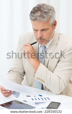 Serious Mature Businessman Concentrating On His Work - stock photo