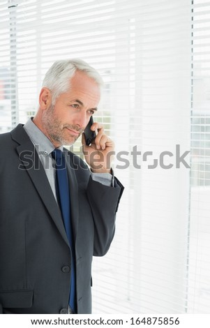 Serious mature businessman peeking through blinds while on call in office - stock photo