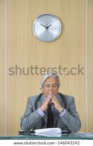 Serious mature businessman reading papers at desk in office - stock photo