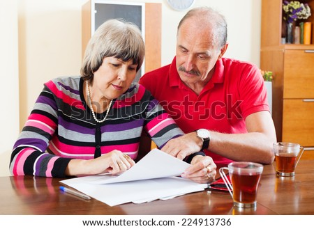 serious mature couple reading financial document - stock photo
