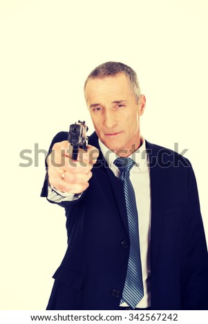 Serious mature mafia agent aiming by handgun. - stock photo
