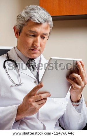 Serious mature male doctor in lab coat looking at digital tablet - stock photo