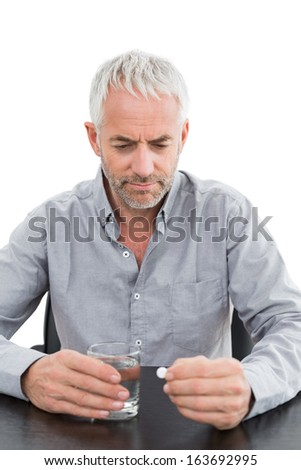 Serious mature man holding glass of water and pill at the table against white background