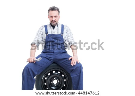 Serious mechanic with spanner sitting on car tire as professional repairman concept isolated on white background with advertising area - stock photo