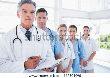 Serious medical team in row in a bright hospital - stock photo