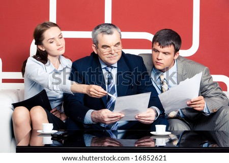 Serious men looking with interest into business plan in chiefâ??s hands at which pretty woman pointing while sitting on sofa - stock photo