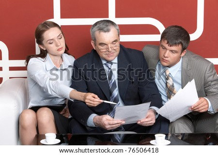 Serious men looking with interest into business plan in chief?s hands at which pretty woman pointing while sitting on sofa - stock photo