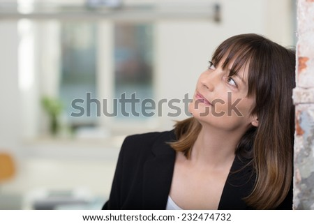 Serious Middle Age Businesswoman in Black Coat Leaning Head on Wall While Looking Up, Thinking of Something. - stock photo
