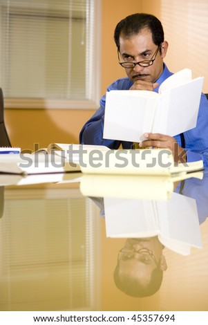 Serious middle-aged Hispanic businessman busy working in boardroom contemplating - stock photo