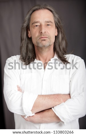 Serious middle-aged man with shoulder length hair standing with his arms folded looking at the camera, upper body studio portrait - stock photo