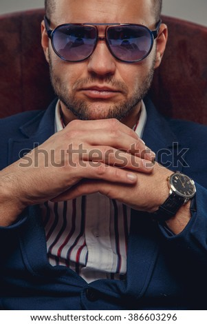 Serious modern businessman in sunglasses.