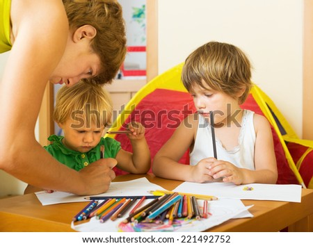 Serious mother and children drawing with pencils at home - stock photo