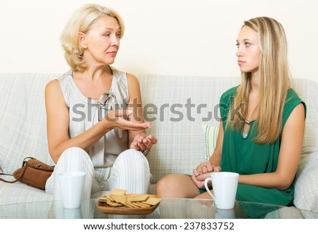 Serious mother and daughter talking in home - stock photo
