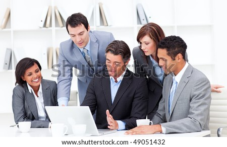 Serious multi-ethnic business partners working at a laptop in the office