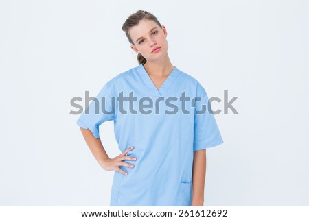 Serious nurse in blue scrubs posing with hand on hip on white background - stock photo
