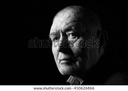 serious old man senior on black background, monochrome - stock photo