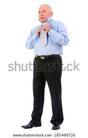 Serious old mature businessman ties a tie. isolated on white background.  - stock photo