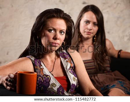 Serious pair of Caucasian brunette females sitting together - stock photo