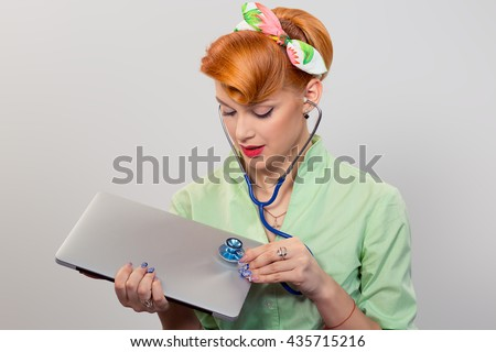 Serious pinup girl listening computer with stethoscope looking at pc retro vintage hairstyle Healthcare diagnosis software repair diagnostics internet threat security safety problem solving concept - stock photo