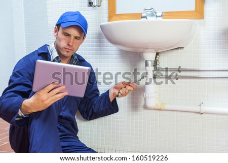 Serious plumber consulting tablet in public bathroom - stock photo