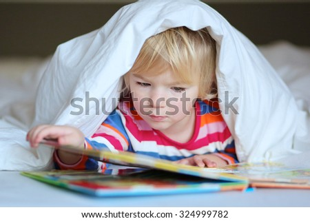 Serious preschooler girl reading book in bed. Cute kid lying under the blanket. Early learning and children development concept.