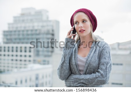 Serious pretty blonde on the phone outdoors on urban background - stock photo
