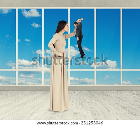 serious pretty woman looking at sad small man. photo in empty room with big windows - stock photo