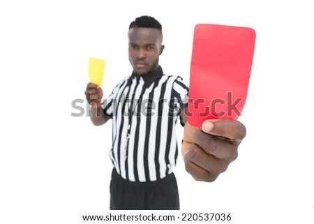 Serious referee showing yellow and red card over white background