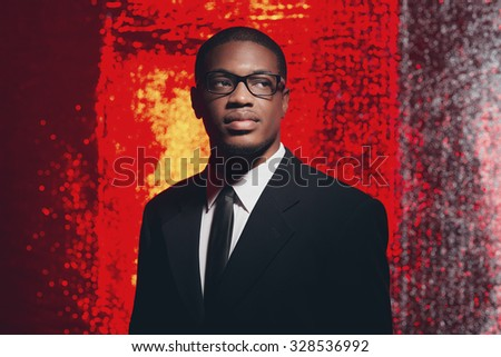 Serious retro fifties hispanic businessman with glasses in front of red reflective background. - stock photo