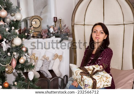 Serious Rich Young Woman Sitting on Elegant Big Chair Doing Giving Presents Sign Near Christmas Tree, while Looking at the Camera