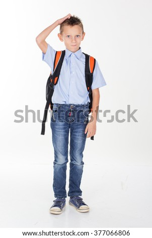 Serious school boy scratching his head - stock photo