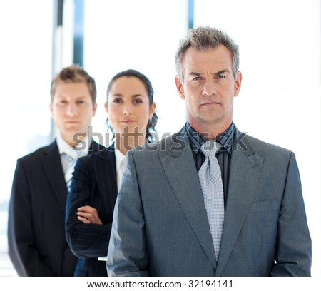 Serious senior businessman leading a business team - stock photo