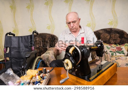 Serious Senior Man Sitting in Living Room Next to Wheelchair with Old Fashioned Sewing Machine and Sewing Supplies - stock photo