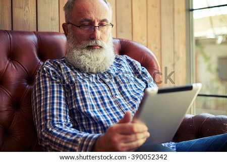 serious senior man sitting on couch and using tablet pc at home - stock photo