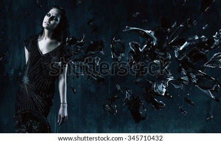 serious sexy woman in black dress with pieces of glass in dark room - stock photo