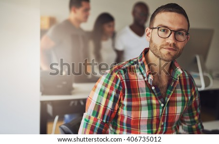 Serious single male business owner wearing multi-colored flannel button shirt with three workers on computer in background - stock photo