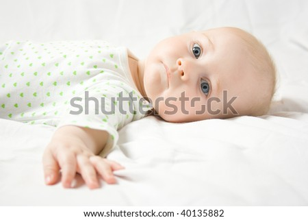 Serious six month old baby dressed in white dress with green hearts looks at you portrait