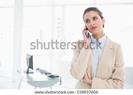 Serious smart brown haired businesswoman making a phone call in bright office - stock photo