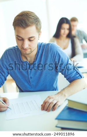 Serious student ticking right answers in question sheet - stock photo