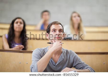 Serious students listening during a lecture with the camera focus on the foreground - stock photo