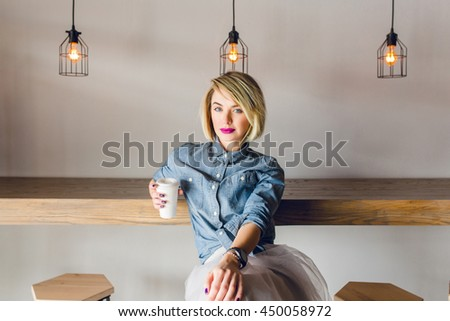 Serious stylish girl with blonde hair and pink lips sitting in a coffee shop with wooden chairs and table. She wears blue denim shirt and grey tulle skirt. She holds a cup of coffee - stock photo
