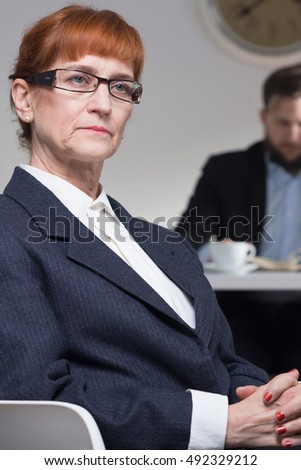 Serious, stylish mature businesswoman in suit sitting on chair