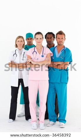 Serious team of doctors looking at the camera with folded arms - stock photo