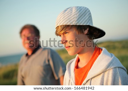 Serious teen with father - stock photo