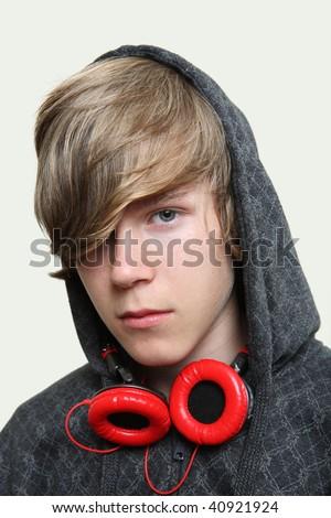 Serious teenage boy wearing headphones on a tan background - stock photo
