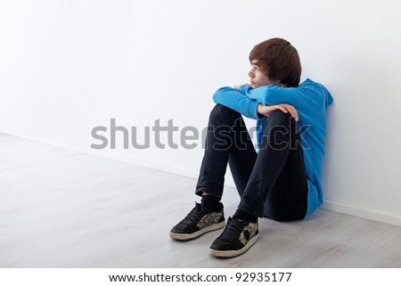 Serious teenager boy thinking and daydreaming while sitting at home - stock photo