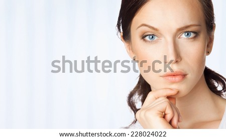 Serious thinking or planning young business woman, at office, with blank area for sign or copyspase - stock photo