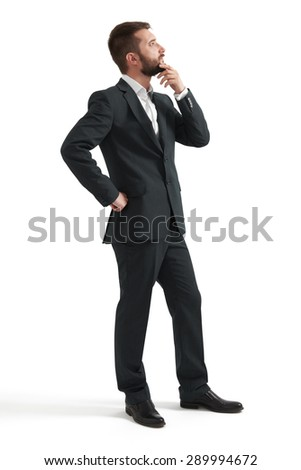 serious thoughtful businessman in formal wear holding his hand at chin and looking up. isolated on white background - stock photo