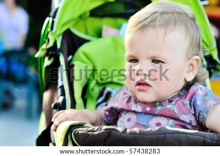 serious toddler girl sitting in the stroller