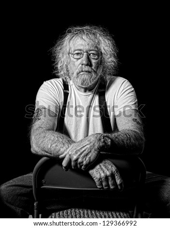 Serious tough old man with wild hair in monochrome isolated on black - stock photo